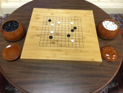 The Library's Go set features a heavy bamboo board and natural stone playing pieces.